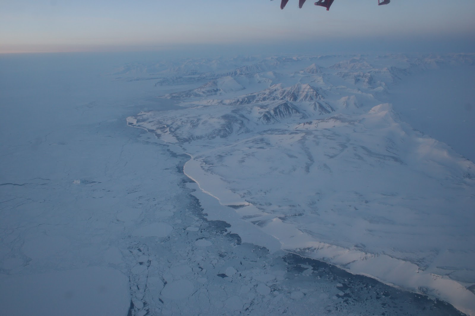 The Eastern coast of Greenland. Sea ice to the left, a snowy beach in the middle, and inland mountains to the right!