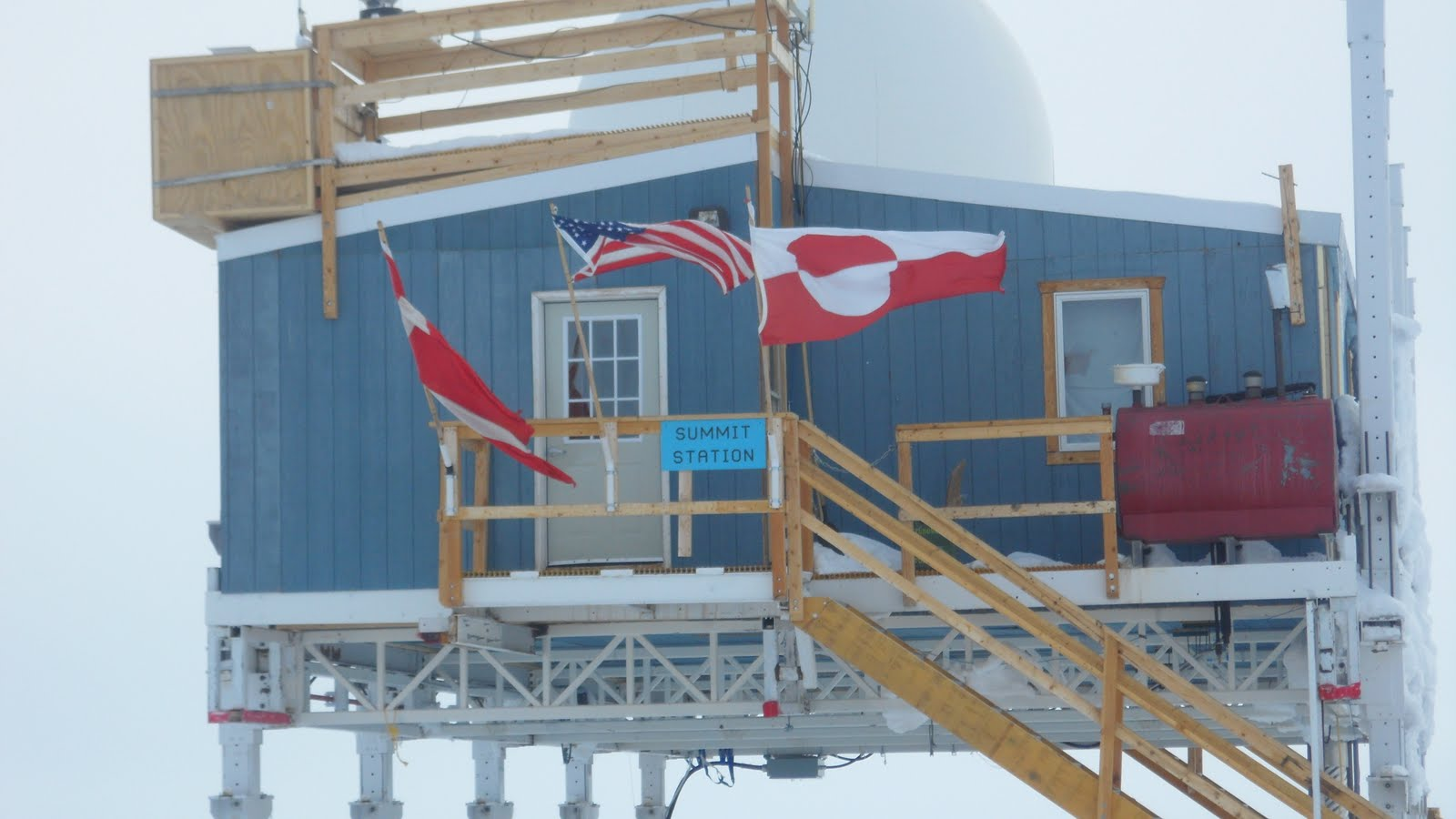 A view of the Big House. The oldest building at Summit. The flags honor the cooperative effort between the United States, Denmark, and Greenland.