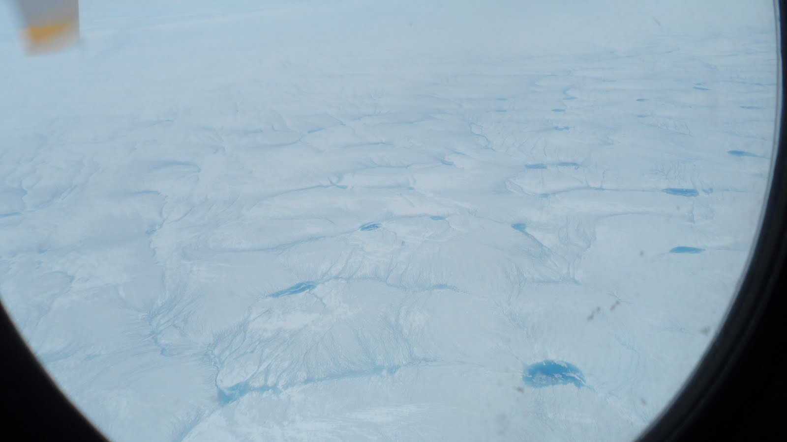 Near the edge of the Ice Sheet, spectacularly colored blue melt ponds and streams can be seen from the window of the C-130